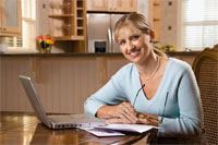 Smiling Woman Sits in Front of Computer at Table